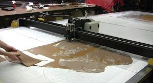 A computer-controlled Gerber cutting machine cuts leather.