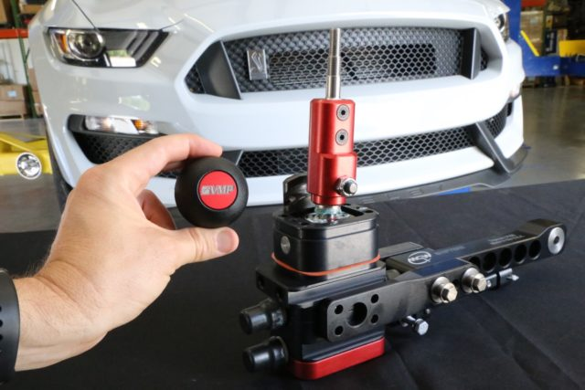 """Want better shifting performance in your 2015+ Shelby GT350? MGW Shifters upgrade (PN MGW-RACESPEC15GT350; $450) is said to hold the shift linkage and transmission in """"perfect alignment at all times to deliver unmatched shifting precision."""" This work of billet art is compatible with the factory shift knob (via and adapter) or one of MGW's own knobs, like the VMP-emblazoned Gripper knob (PN MGW-SHIFTKNOB; $50) shown here."""